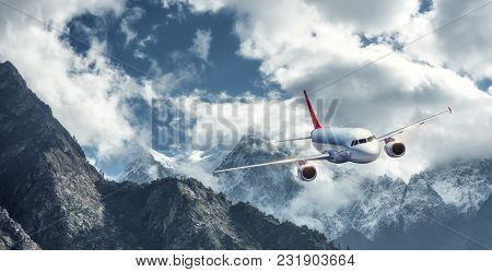 Airplane Is Flying Over Low Clouds Against Mountains