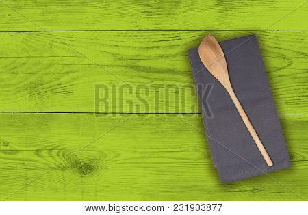 Wooden Spoon And Kitchen Towel On Green Wood.