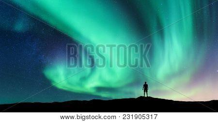 Aurora Borealis And Silhouette Of Standing Man. Lofoten Islands, Norway. Aurora And Happy Man. Sky W