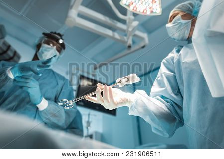 Bottom View Of Doctor Passing Medical Clamp To African American Surgeon