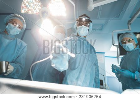 Bottom View Of Multicultural Surgeons Looking At Camera During Surgery