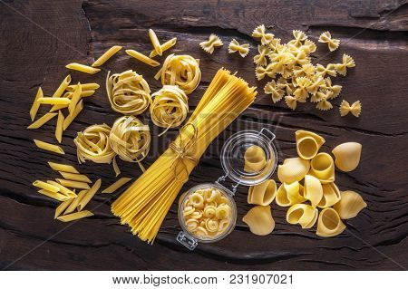 Different pasta types on the wooden table. Pasta background.