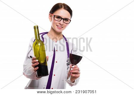 Portrait Of Young Attractive Female Doctor In White Coat Smiling Looking In Camera Holding Bottle An