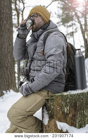 Handsome, Bearded Man In Glasses With A Camera And A Backpack Sitting On A Tree Stump In The Winter