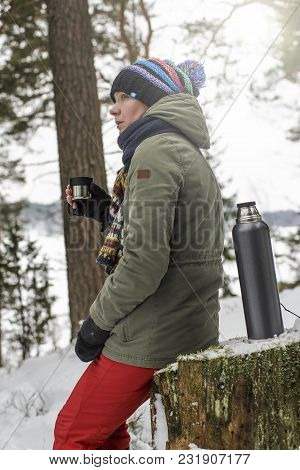 Cute Woman Sitting On A Stump In The Winter Forest, Holding A Cup With A Hot Drink From A Thermos An