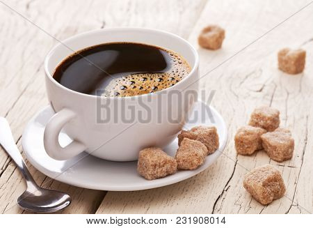 Coffee cup and brown sugar cubes on the wooden table.