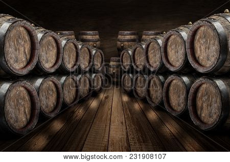 Oak wine barrels in the wine cellar. Old stone wall at the background. Wine background.