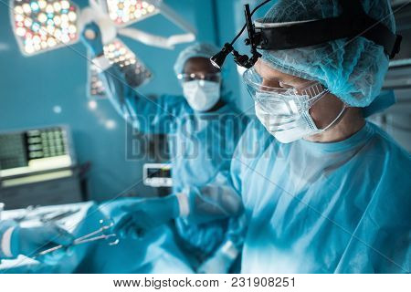 Cropped Image Of Nurse Passing Medical Scissors To Surgeon In Operating Room