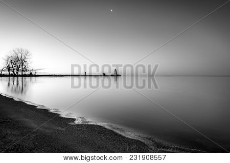 Moody Calm Shoreline With Still Waters Reflecting In Early Morning Light. Trees, Moon And Lighthouse