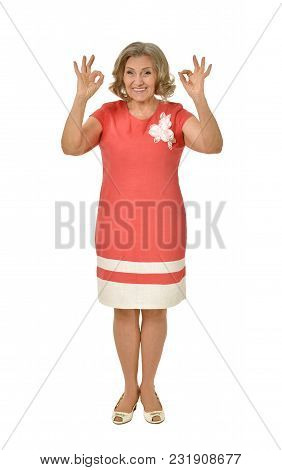 Portrait Of Senior Woman In Pink Dress Showing Ok Sign Isolated On White Background