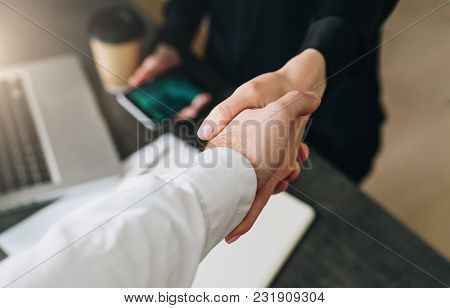 Close-up Of Handshake Of Businessman And Businesswoman. Man's Hand Shakes Woman's Hand.successful Co