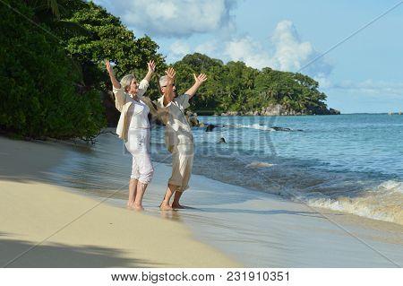 Happy Elderly Couple Resting In Tropical Garden Outdoors