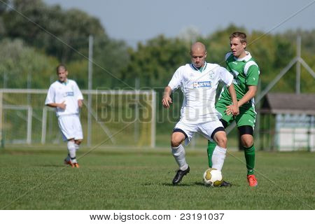 KAPOSVAR, HUNGARY - SEPTEMBER 5: Attila Kiss (white 5) in action at the Hungarian National Championship under 19 game Kaposvar (white) vs. Nagyatad (green) September 5, 2011 in Kaposvar, Hungary.