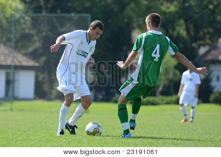 KAPOSVAR, HUNGARY - SEPTEMBER 5: Kristof Kovacs (green 4) in action at the Hungarian National Championship under 19 game Kaposvar (white) vs. Nagyatad (green) September 5, 2011 in Kaposvar, Hungary.