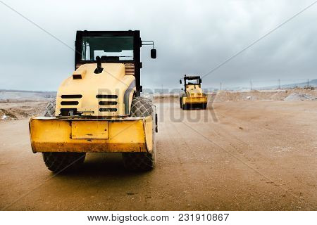Two Vibratory Soil Compactors On Construction Site. Industrial Roadworks At Highway With Heavy-duty