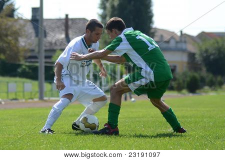 KAPOSVAR, HUNGARY - SEPTEMBER 5: Daniel Pager (in white) in action at the Hungarian National Championship under 19 game Kaposvar (white) vs. Nagyatad (green) September 5, 2011 in Kaposvar, Hungary.