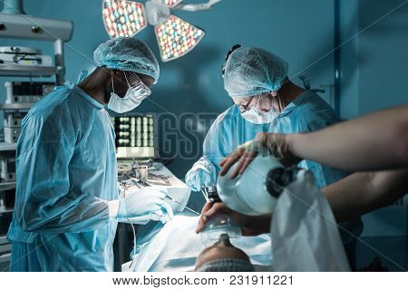 Multiethnic Surgeons And Patient In Operating Room