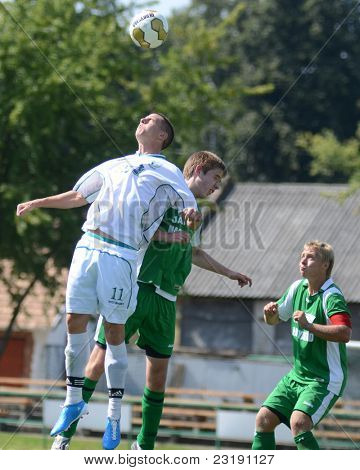 KAPOSVAR, HUNGARY - SEPTEMBER 5: Daniel Vaszilko (in white) in action at the Hungarian National Championship under 19 game Kaposvar (white) vs. Nagyatad (green) September 5, 2011 in Kaposvar, Hungary.