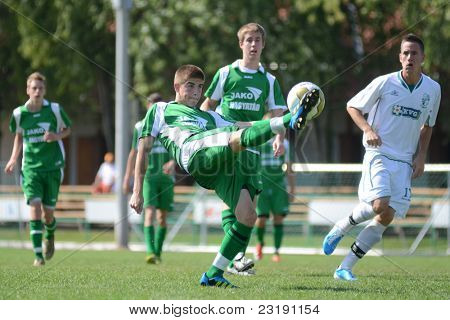 KAPOSVAR, HUNGARY - SEPTEMBER 5: Kristof Kovacs (C) in action at the Hungarian National Championship under 19 game Kaposvar (white) vs. Nagyatad (green) September 5, 2011 in Kaposvar, Hungary.