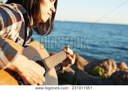 Young man with guitar playing music by seaside on summer day