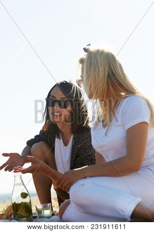 Friendly guy and girl having talk while enjoying picnic on summer day by seaside