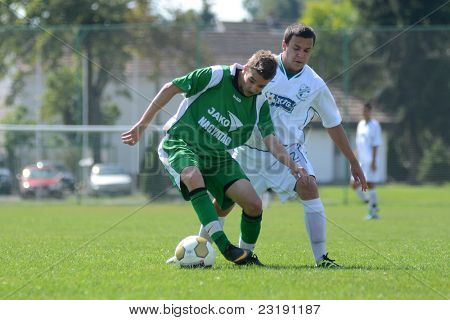 KAPOSVAR, HUNGARY - SEPTEMBER 5: Laszlo Tulok (white 12) in action at the Hungarian National Championship under 19 game Kaposvar (white) vs. Nagyatad (green) September 5, 2011 in Kaposvar, Hungary.