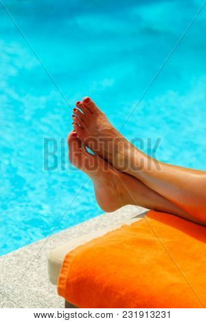 Woman feet at the pool on a hot summer day
