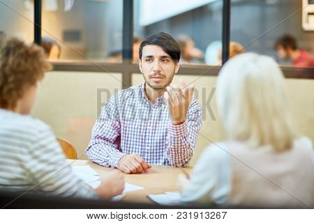 Young applicant explaining his objectives while talking to employers during interview in office