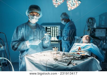 Surgeon Cleaning Surgical Tweezers And Looking At Camera In Surgery Room