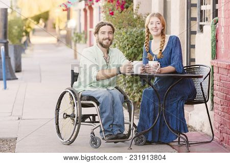 Woman Having Coffee With Male Friend In Wheelchair