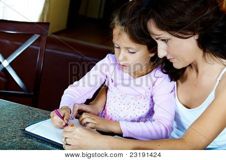 Yong brunette mother in her thirties helping her daughter with drawing homework while sitting at home.