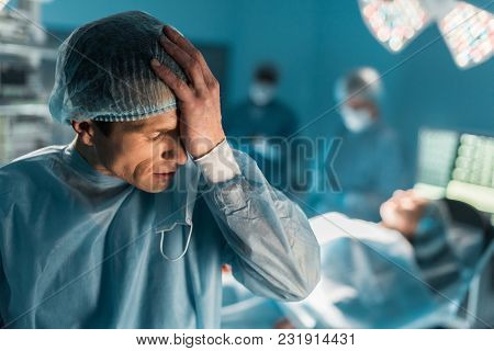 Tired Surgeon Touching Head In Operating Room