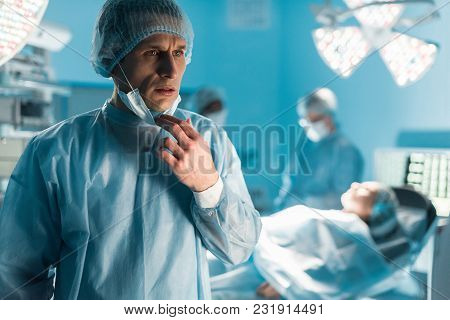 Scared Surgeon Looking Away In Operating Room