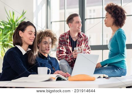 Four young students watching together a funny online video on a laptop during break in the classroom of a modern college or university