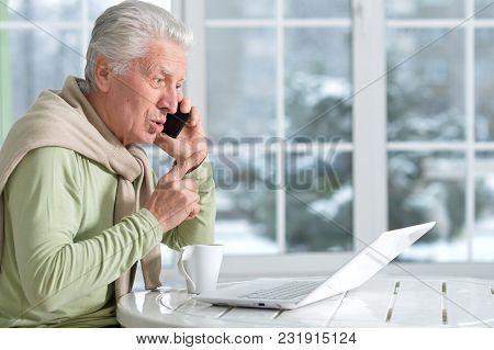 Portrait Of Mature Man With Phone Using Laptop