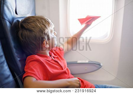 Little Kid Boy Playing With Red Paper Plane During Flight On Airplane. Child Sitting Inside Aircraft
