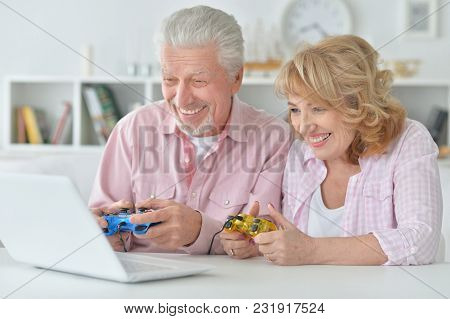 Happy Senior Couple Playing Computer Game With Laptop