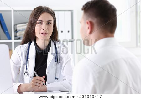 Beautiful Smiling Female Doctor Hold Silver Pen Filling Patient History List At Clipboard Pad. Physi