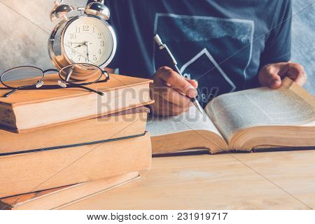 A Man Reding Text Book With Clock And Glasses  On Stack Books