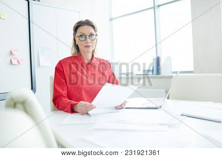 Confident mid-aged employer sitting by desk in her office while waiting for new applicant to come