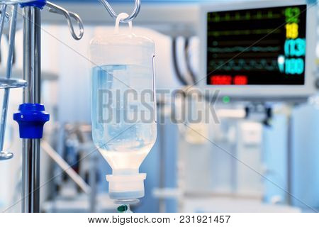 Medical Drip with ECG Monitor at Background in Hospital Ward