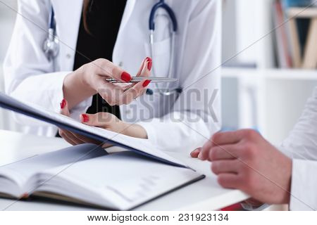 Female Doctor Hand Hold Silver Pen And Showing Pad. Physical Agreement Form Signature Disease Preven