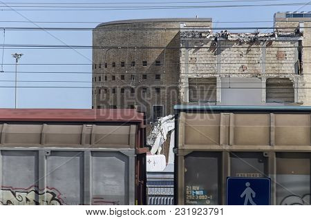 Train Passing In Front Of A Demolished Building
