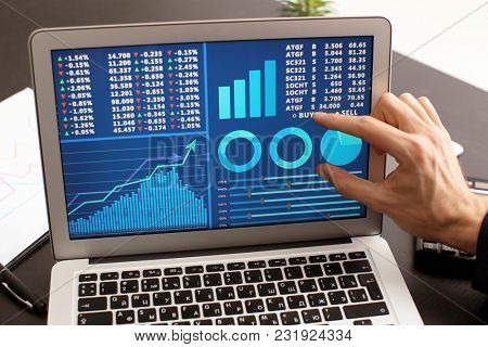 Man using laptop with stock chart data on screen. Forex concept