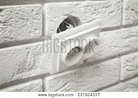 Old electric socket hanging out of brick wall