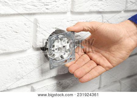 Electrician repairing socket on brick wall