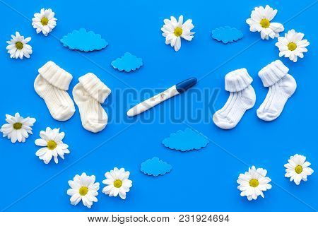 Waiting For A Baby With Positive Pregnancy Test And Flowers On Blue Background Top View