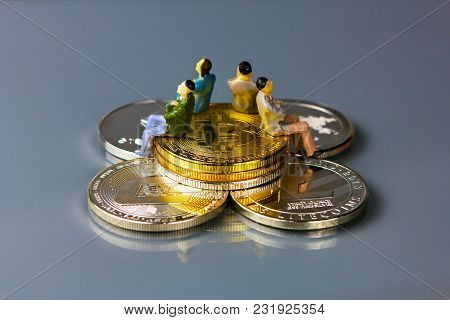 Coins Of Different Crypto-currencies With Statuette People Sitting On Them.