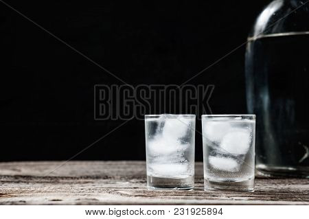 Cold Vodka In Shot Glasses On A Black Background On Wooden Table Closeup With Copyspace