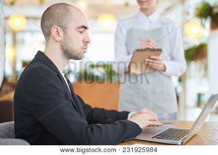 Businessman typing on laptop with waiter taking an order